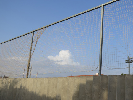 Wolk achter foorball stadionnetting in Andalusisch dorp Stockfoto