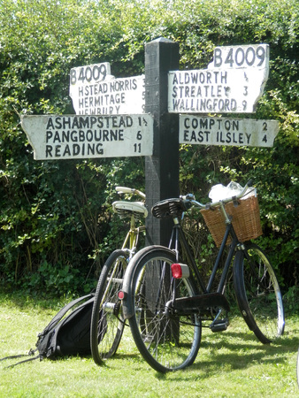 Bicycles leaning on four points signpost in village of Aldworth, Berkshire, England Stock Photo