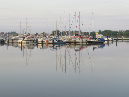 Moored Sailing boats in late afternoon sun in inlet in southeast Denmark