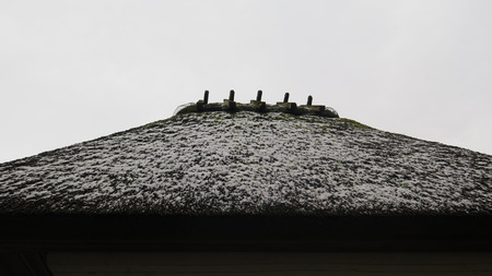Snow covered thatched roof on small building in southern Denmark Banque d'images