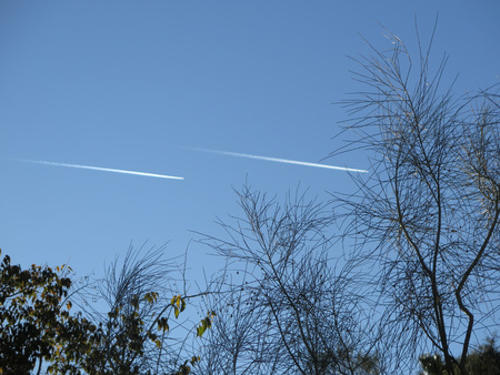 Airplane vapour trail at dawn over hills