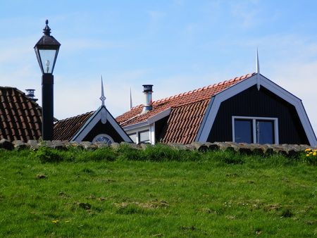 Houses protected behind grass covered dike in Dutch fishing village