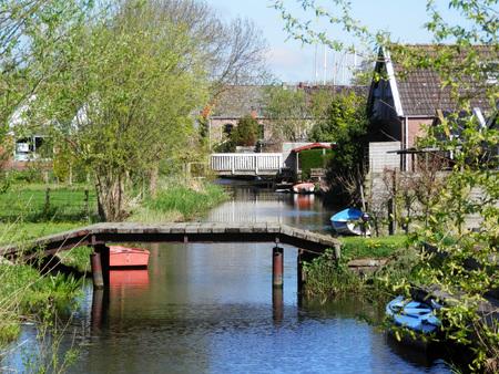 Wooden footbridge over canal in dutch fishing village
