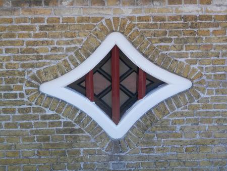 Brick surround Diamond shaped window with bars in Dutch fishing village