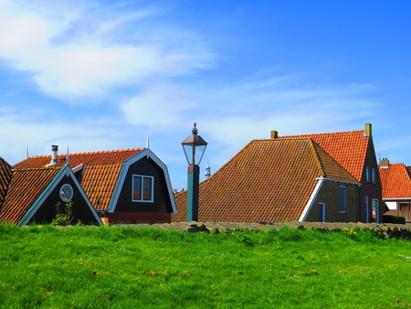 Houses protected behind grass covered dike in Dutch fishing village of Hindeloopen