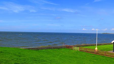 Green grass covered dike in Dutch fishing village Stockfoto