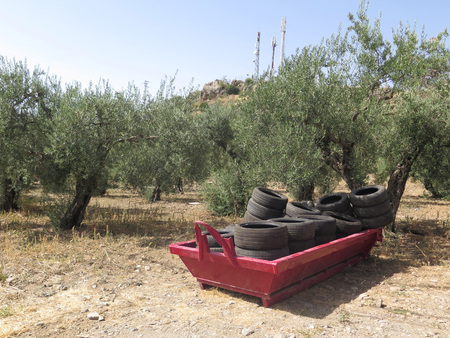 Red builders skips with rubber tires on wasteland near Alora Andalusia Foto de archivo