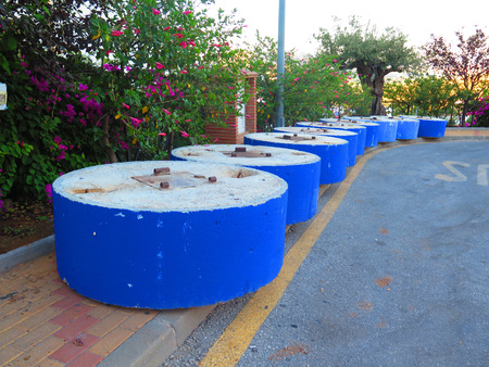 Circular Blue painted concrete bases ready for erecting sun cover in Andalusian village, Spain