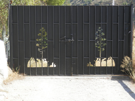 Black Metal double gate with stencilled out trees in Granada suburb, Andalusia Foto de archivo