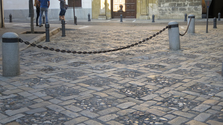 Heavy steel chain across large cobble stone square in Granada, Andalusia