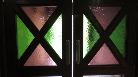 Colored glass windows in swing doors in Andalusian village restaurant