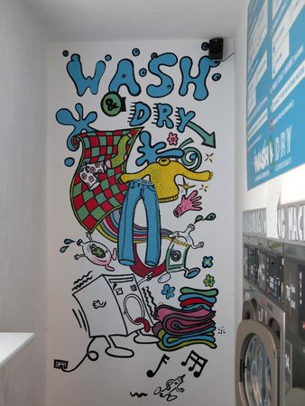 Fuengirola, Spain - October 3, 2018: Hand painted fun cartoons on laundrette wall Editorial