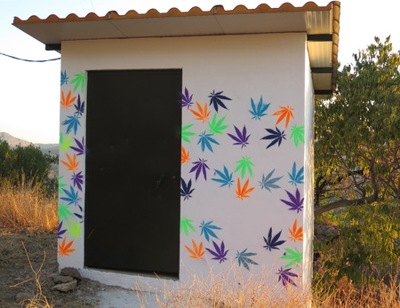 Alora, Spain - October 5, 2018: Colorful cannabis leaves stencilled onto brick built hut in Andalusian countryside Editorial