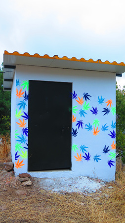 Alora, Spain - October 8, 2018: Colorful cannabis leaves stencilled onto brick built hut in Andalusian countryside Editorial