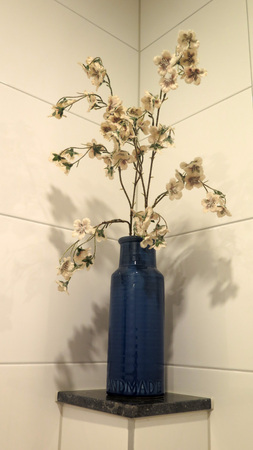 Decorative stylish artificial flowers in blue bottle against tiled wall