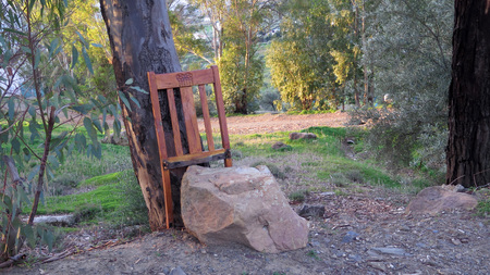 Back of broken chair used as back rest for flat rock in Andalusian village