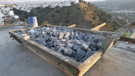 Builders skip with new square cobble stones at new viewpoint construction site in Andalusian village