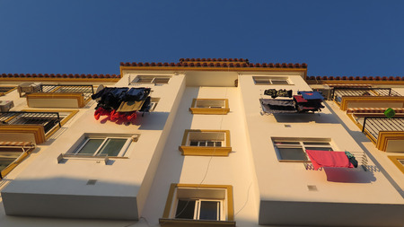 Washing drying on lines outside apartments in large block in Andalusian village Imagens