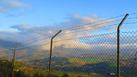 Valley view through chain link fence topped with rows of barbed wire in Andalusia Stock fotó