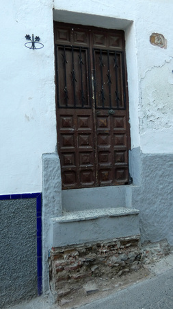 Dangerous exit from house with missing bottom step in Andalusian village