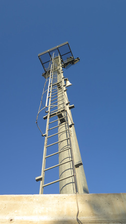 Tall flood lighting mast against blue Andalusian spring sky