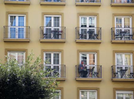 Malaga, Spain - March 13, 2019: Man eating breakfast on small balcony in Malaga apartment building