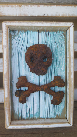 Scull and crossbone wall hanging made from smelted rusty iron Stock Photo