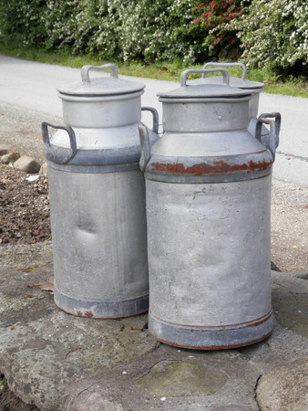 Three old milk churns by village lane insouthern Denmark