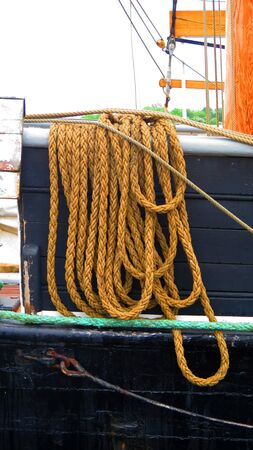 Coiled mooring ropes on tall ship in southern Danish harbor of Graasten