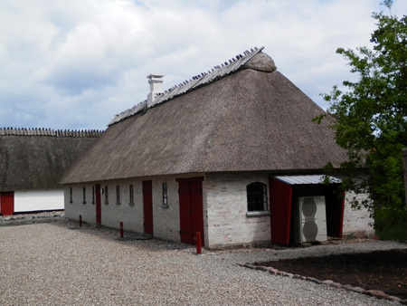 Holm, Denmark - May 27, 2019: Thatched farmhouse building on cobbled street in old Southern Danish villaage Editorial