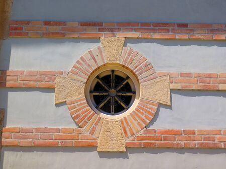 Brick surround round circular shaped window with bars in Andalusian village Фото со стока