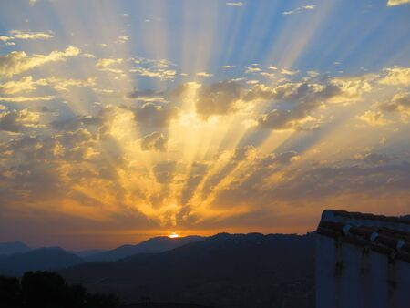 Rising sun casting rays on clouds in early morning Andalusian countryside