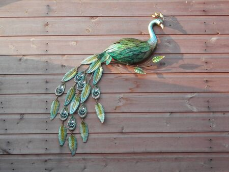 Closeup of ceramic peacock on wood shed background Standard-Bild