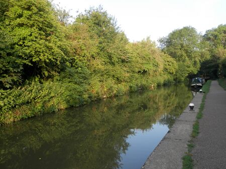 Narrowboat moored by tow path on Grand Union canal at Stoke Bruerne, England