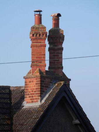 Two tall brick built chimneys against blue English summer sky 版權商用圖片