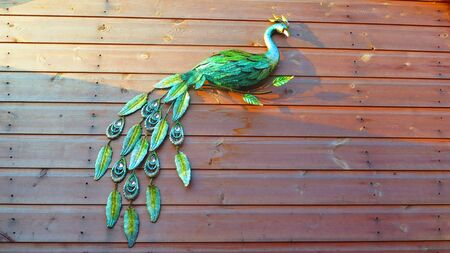 Closeup of green ceramic peacock on wood shed background