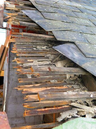 Closeup of old slates and broken wooden supports at roof replacement project Banque d'images
