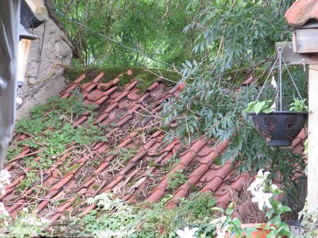 Overhang with demolished roof tiles at village house in English village