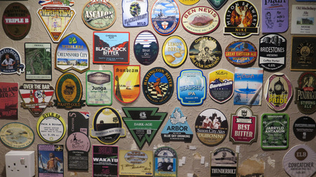 Reading, United Kingdom - August 9, 2019: Ale house walls and ceiling covered in colorful beer mats
