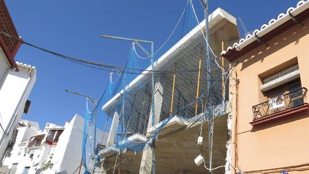 New building site with blue protective blue netting cover on village brown site