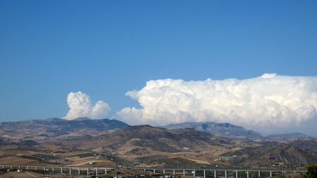 Large white cloud over Andalusian valley with high speed railway viaduct