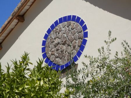 Large gable decoration of blue tile circle with stone block centre in Andalusian village