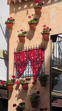 Artificial wall decorated with flowers, shawls and balcony for annual soup day in Alora, Andalusia