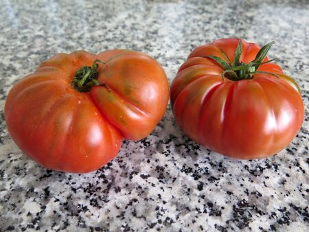Top view of two large red tomatoes on marble kitchen work top 版權商用圖片