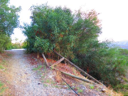 Broken rural fencing lining path above Andalusian village, Spain