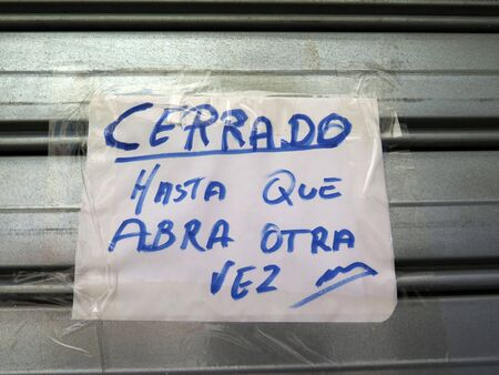 Hand written note in Spanish on shutters of local village bar: Closed until I open again 版權商用圖片