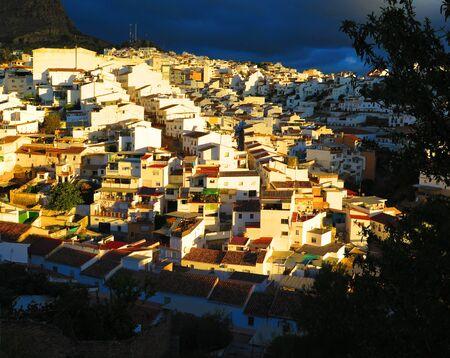 Sun shining on white village of Alora against dark rain clouds