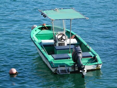 Small green boat with outboard motor and square sun roof