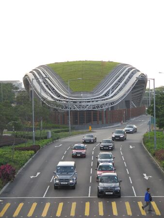 Hong Kong, East Asia - November 15, 2019: Vehicles on Hong Kong ring road with grass covered overhang Stockfoto