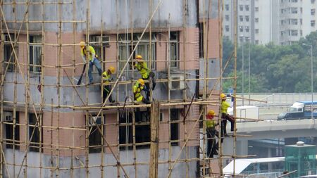 Hong Kong, East Asia - November 26, 2019: Intricate bamboo scaffolding being erected by chinese workers in Kowloon business district